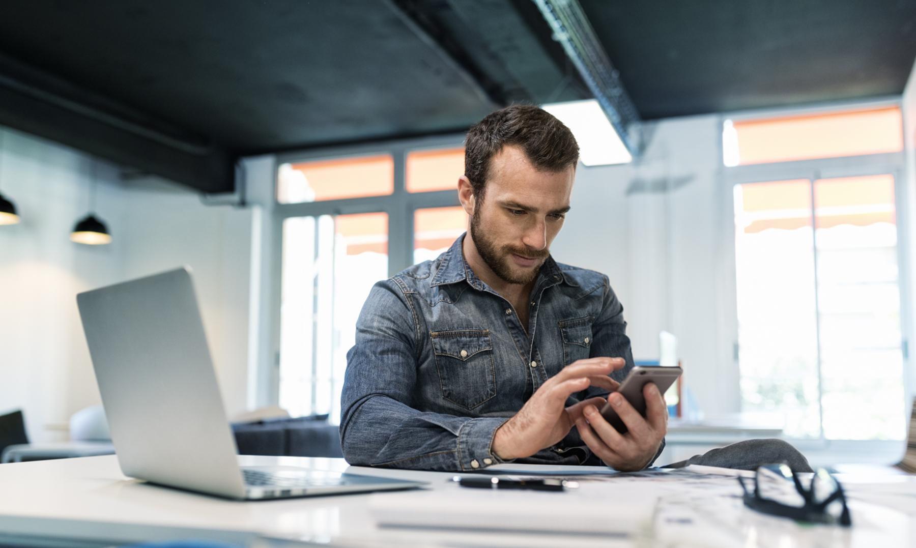 Man in modern office working on laptop.