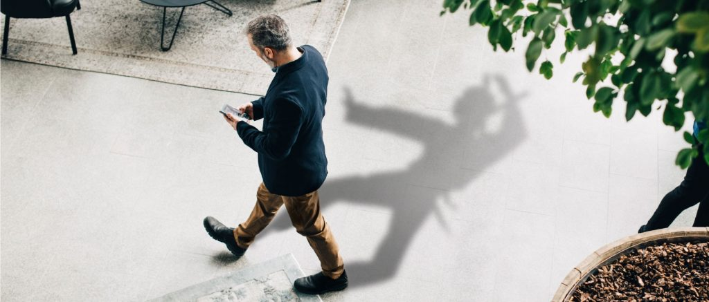man looking at phone with Ninja shadow in the background